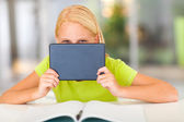 Funny pre teen girl behind tablet computer — Stock Photo