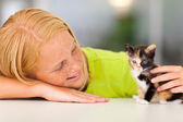 Loving pre teen girl playing with kitten — Stock Photo