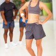 Sporty woman posing with friends gym — Stock Photo