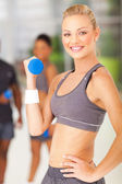 Young fit woman lifting dumbbell — Stock Photo