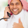 Arabic businessman talking on landline phone and giving thumb up — Stock Photo #25420541