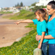 Daughter pointing at ocean with mother at the beach — Stock Photo