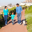 Young couple with their daughter walking pet dog — ストック写真