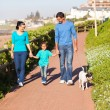 Young couple with their daughter walking pet dog — Stok fotoğraf