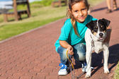 Cute little girl and pet dog outdoors — ストック写真