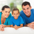 Happy family of three lying on bed — Stock Photo #25520403