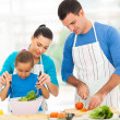 Mother teaching little daughter mixing salad — Stockfoto