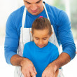 Stock Photo: Father teaching daughter cooking