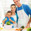 Beautiful young family cooking at home — Stock Photo