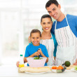图库照片: Adorable young family cooking at home