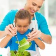 Loving mother teaching daughter mixing salad — Stock Photo #25522301
