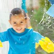 Cute little girl cleaning window glass with parents — Stock Photo