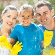 Happy family cleaning window glass — Stock Photo #25523881