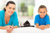 Mother daughter and pet dog lying on bed — Stock Photo