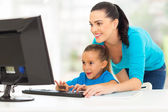 Happy mother teaching daughter computer — Stock Photo