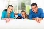 Happy family lying on bed with pet dog — Stock Photo