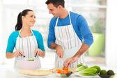 Loving couple chatting while preparing salad — Stock Photo