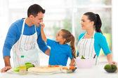 Söta dotter utfodring far en bit tomat — Stockfoto