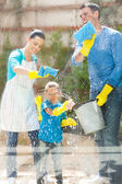 Happy family cleaning home window — Stok fotoğraf