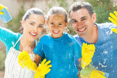 Happy family cleaning window glass — Stock Photo