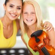 Beautiful music teacher with violin student — Stock Photo