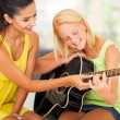 Beautiful music teacher tutoring young girl to play guitar — Stock Photo #26286009