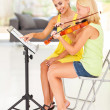 Music teacher pointing notes for violin student — Stock Photo #26286139