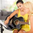 Music teacher tutoring young girl to play guitar - Foto de Stock