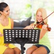 Music teacher tutoring young girl to play violin — Stock Photo #26286377