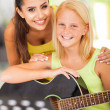 Stock Photo: Friendly teacher with her music learner