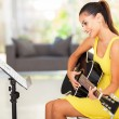 Stock Photo: Young woman playing guitar