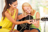 Beautiful music teacher tutoring young girl to play guitar — Stock Photo