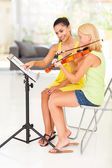 Music teacher pointing notes for violin student — Stock Photo