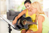 Music teacher tutoring young girl to play guitar — Stock Photo