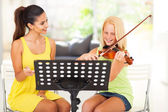 Music teacher tutoring young girl to play violin — Stock Photo