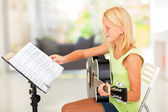 Preteen girl playing guitar with musical chords — Stock Photo