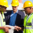 Manager and construction workers examining a brick — Stock Photo