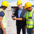 Construction workers with their manager checking bricks — Stock Photo