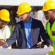 Architect and construction workers on construction site — Stock Photo #26374913