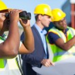Construction worker using binoculars — Stock Photo