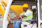 Africa american man operates excavator — Stock Photo