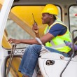 Stock Photo: Afro american man operates excavator