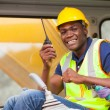 Stock Photo: African bulldozer operator talking on walkie talkie