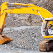 Road construction worker operating excavator - Stock Photo