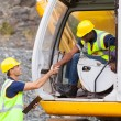 Construction manager handshaking with bulldozer operator — Stock Photo