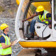 Construction foreman talking excavator operator — Stock Photo