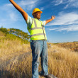 African construction worker with arms outstretched — Stock Photo