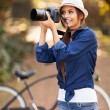Stock Photo: Young womtaking pictures at park
