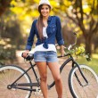 Young woman posing next to bike — Stock Photo #26389609