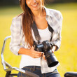 Pretty woman with camera outdoors — Stock Photo
